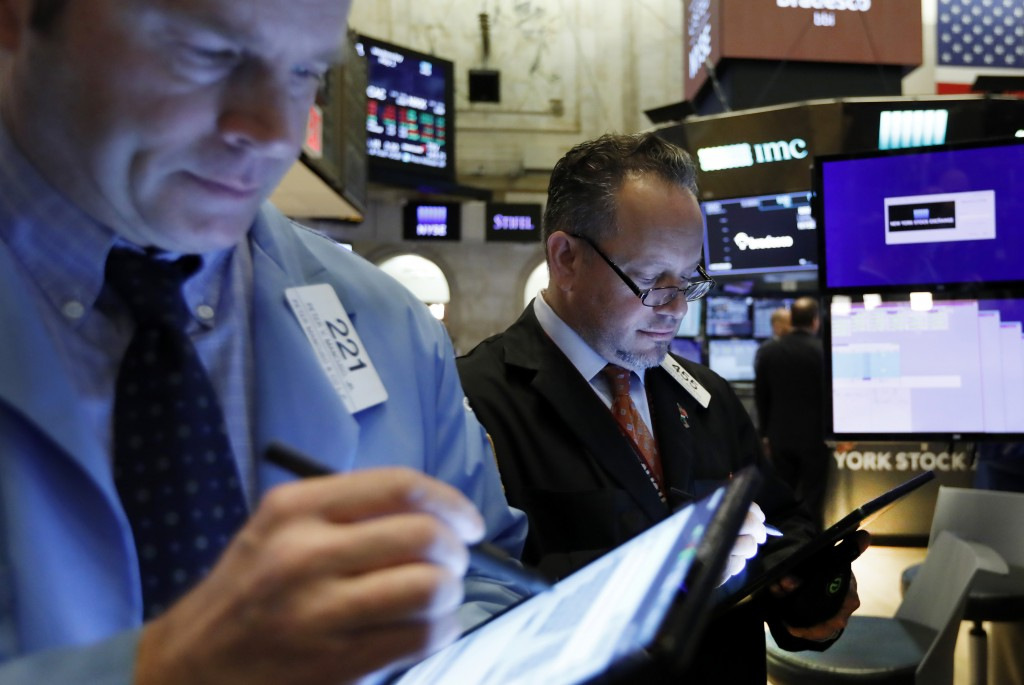 FILE - In this May 1, 2019, file photo traders Peter Mancuso, left, and Robert Arciero work on the floor of the New York Stock Exchange. The U.S. stoc...