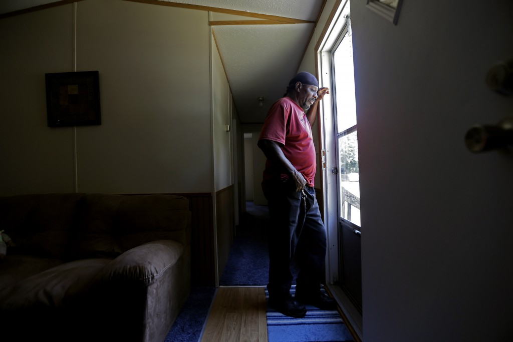 In this photo taken Wednesday, May 29, 2019, resident James Lesane stands at the entrance to his mobile home in Lumberton, N.C. Every month, Lesane pa