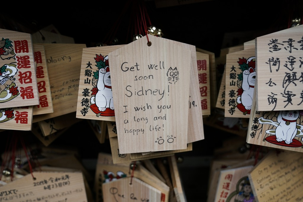 In this July 2, 2019, photo, a prayer is written on a wooden panel donned with an image of a beckoning cat at Gotokuji Temple in Tokyo. According to a...