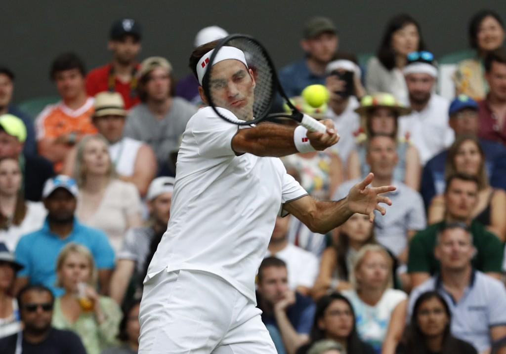 Switzerland's Roger Federer returns the ball to It...