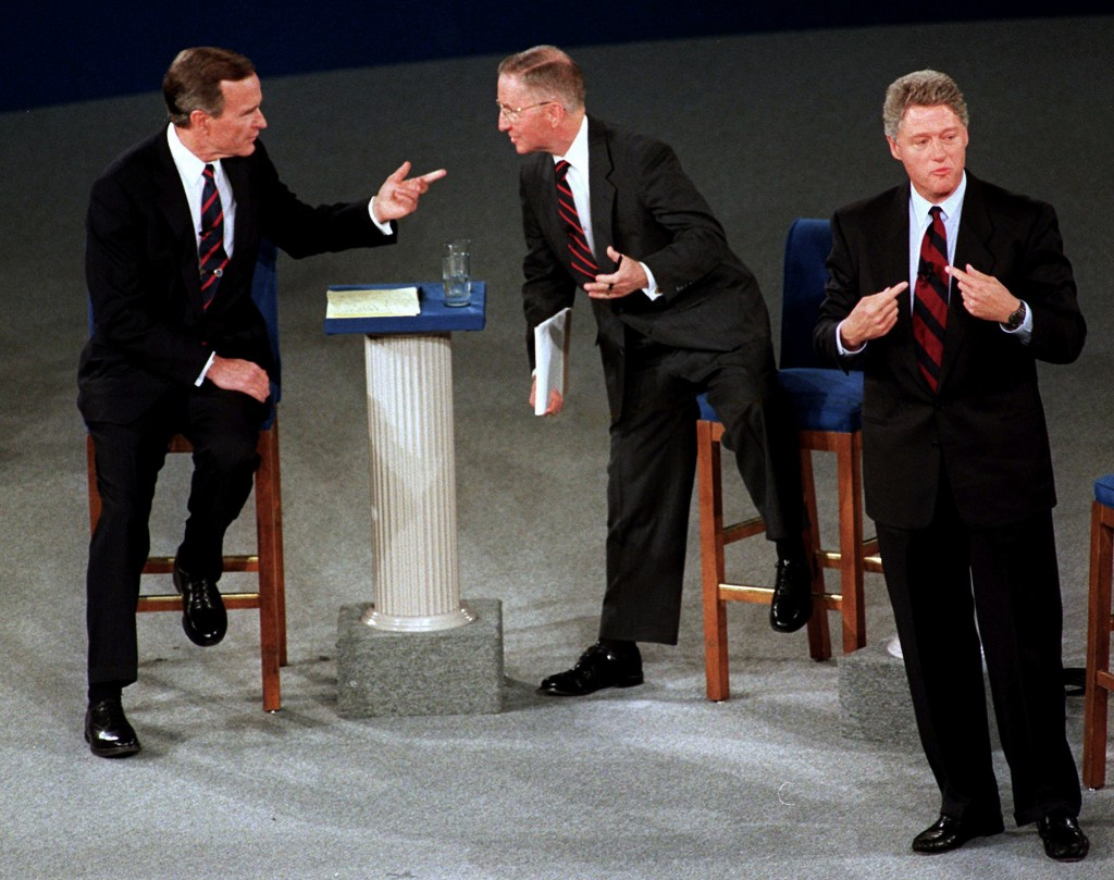 FILE - In this Oct. 15, 1992, file photo, President George H.W. Bush, left, talks with independent candidate Ross Perot as Democratic candidate Bill C