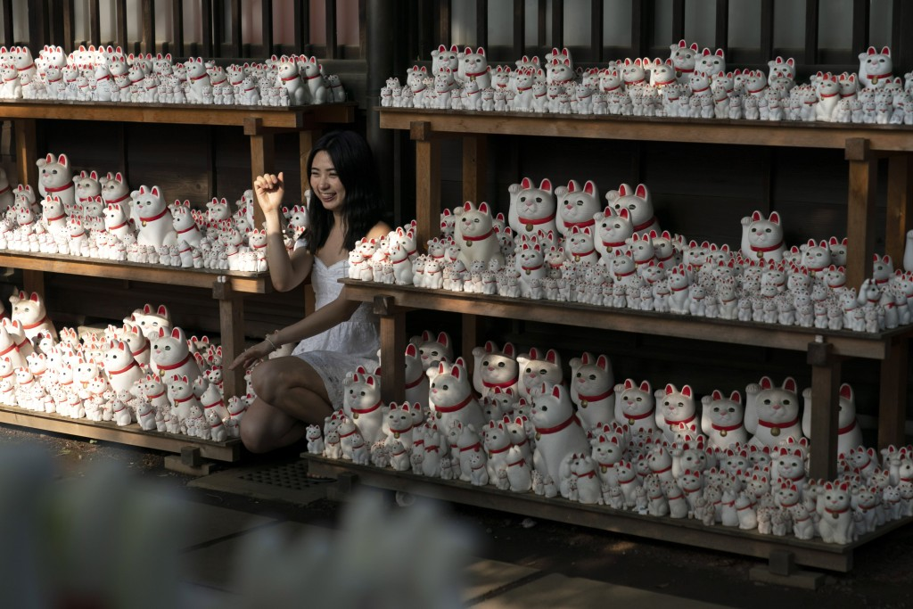 In this June 25, 2019, photo, a woman poses for photos with beckoning cat figurines at Gotokuji Temple in Tokyo. According to a centuries-old legend p...