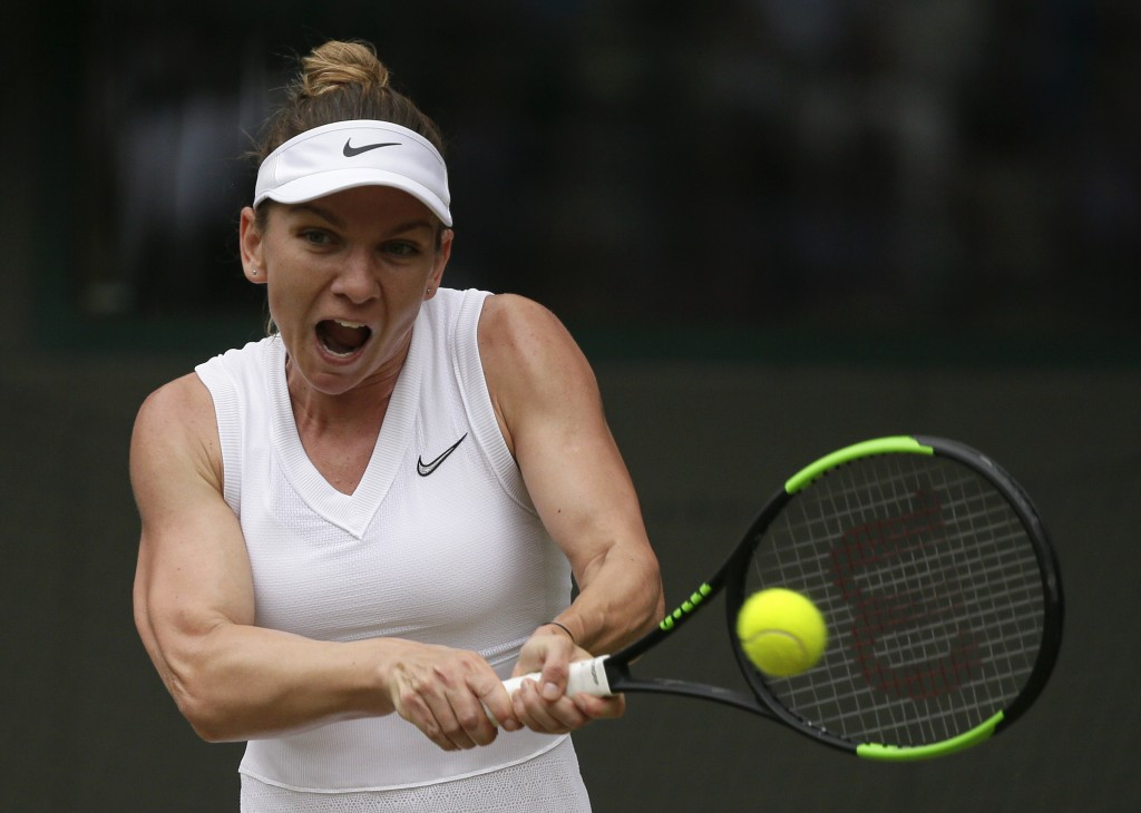 Romania's Simona Halep returns the ball to China's Shuai Zhang during a women's quarterfinal match on day eight of the Wimbledon Tennis Championships ...