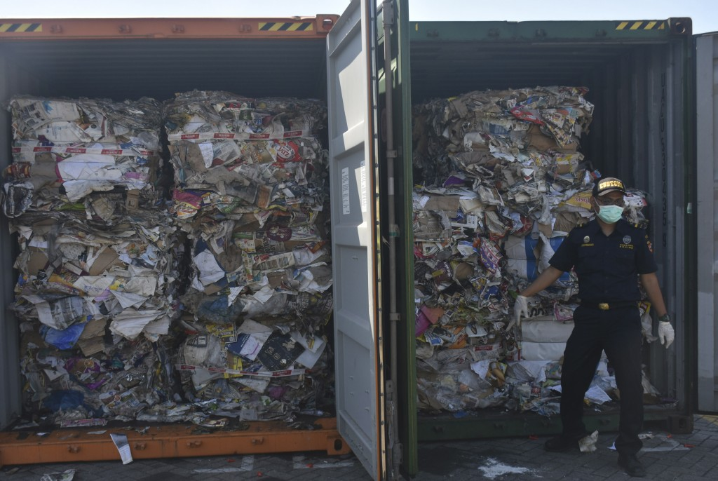 In this Tuesday, July 9, 2019, file photo, custom officers stand near containers of waste at Tanjung Perak port in Surabaya, East Java, Indonesia. Ind...