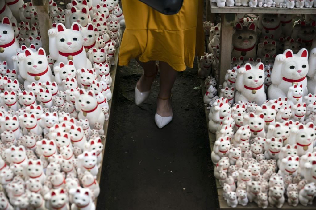 In this June 25, 2019, photo, a tourist walk between beckoning cat figurines after posing for photos with them at Gotokuji Temple in Tokyo. According ...