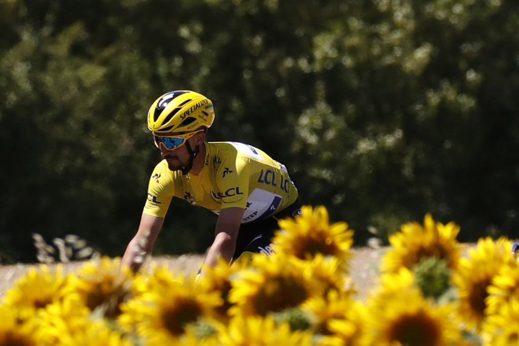 France's Julian Alaphilippe wearing the overall leader's yellow jersey rides next to a field of sunflowers, during the fourth stage of the Tour de Fra...