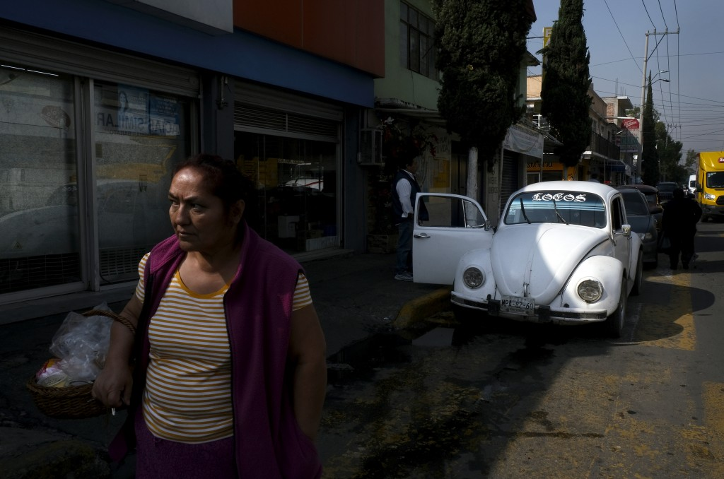 "A Volkswagen Beetle is parked in a taxi lane as drivers wait for clients in a neighborhood of Mexico City known colloquially as ""Vocholandia,"" for its"