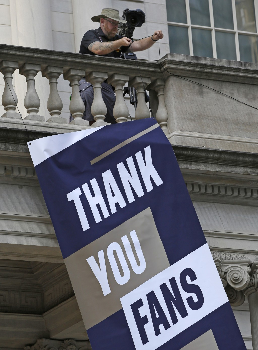 A worker hangs a banner from the balcony at New Yo...