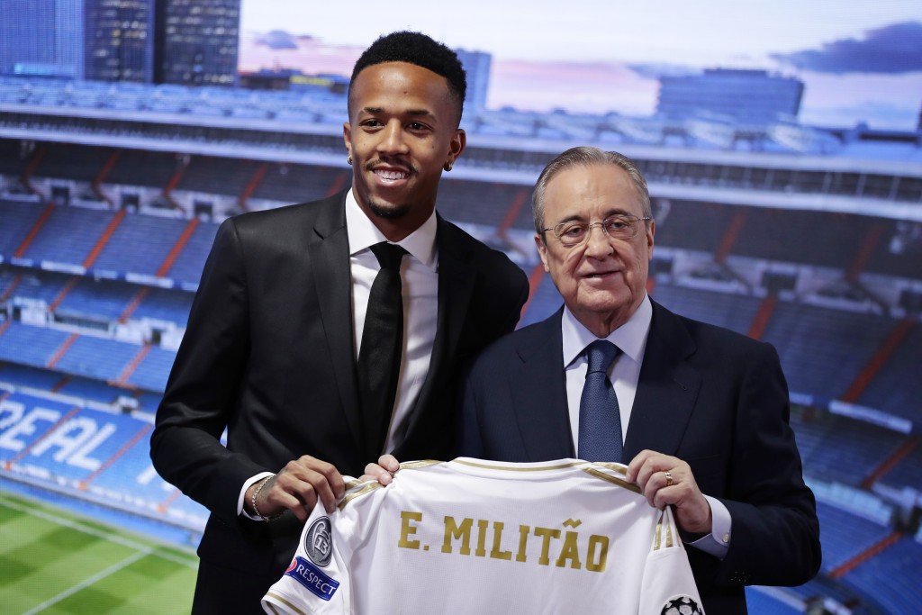 Eder Militao, left, holds up his new team shirt with Real Madrid's President Florentino Perez during his official presentation after signing for Real