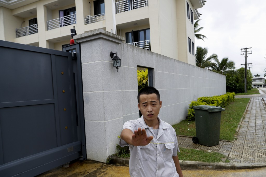In this Monday, April 8, photo, a Chinese Embassy staff member gestures to stop taking photos outside the embassy accommodation building in Nuku'alofa