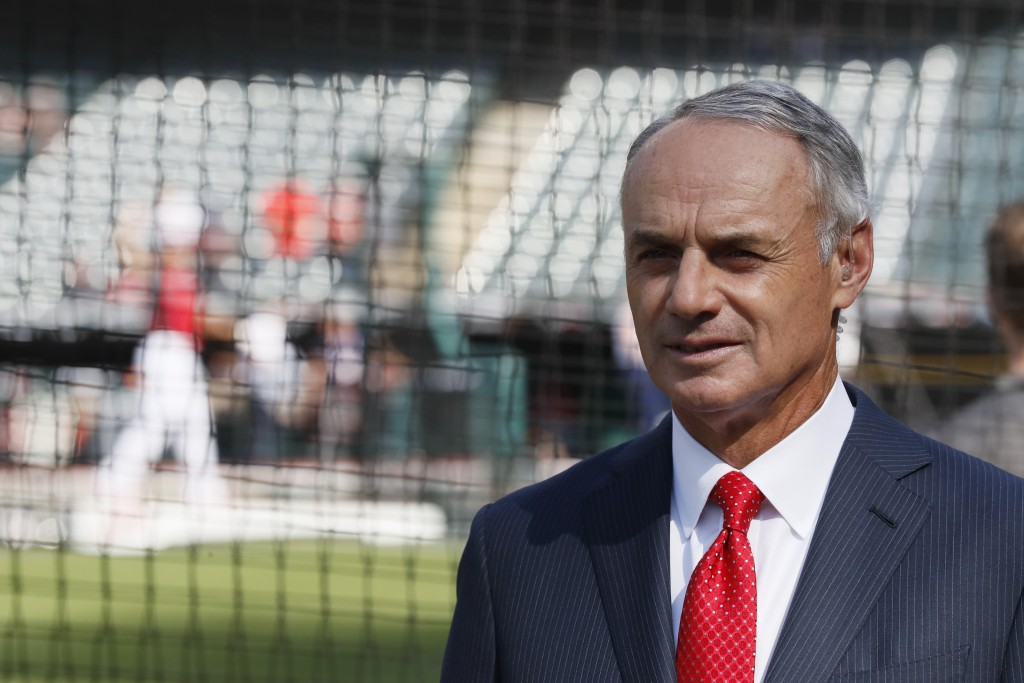 Commissioner Rob Manfred watches as the American League players warm-up for the MLB baseball All-Star Game, Tuesday, July 9, 2019, in Cleveland. (AP P