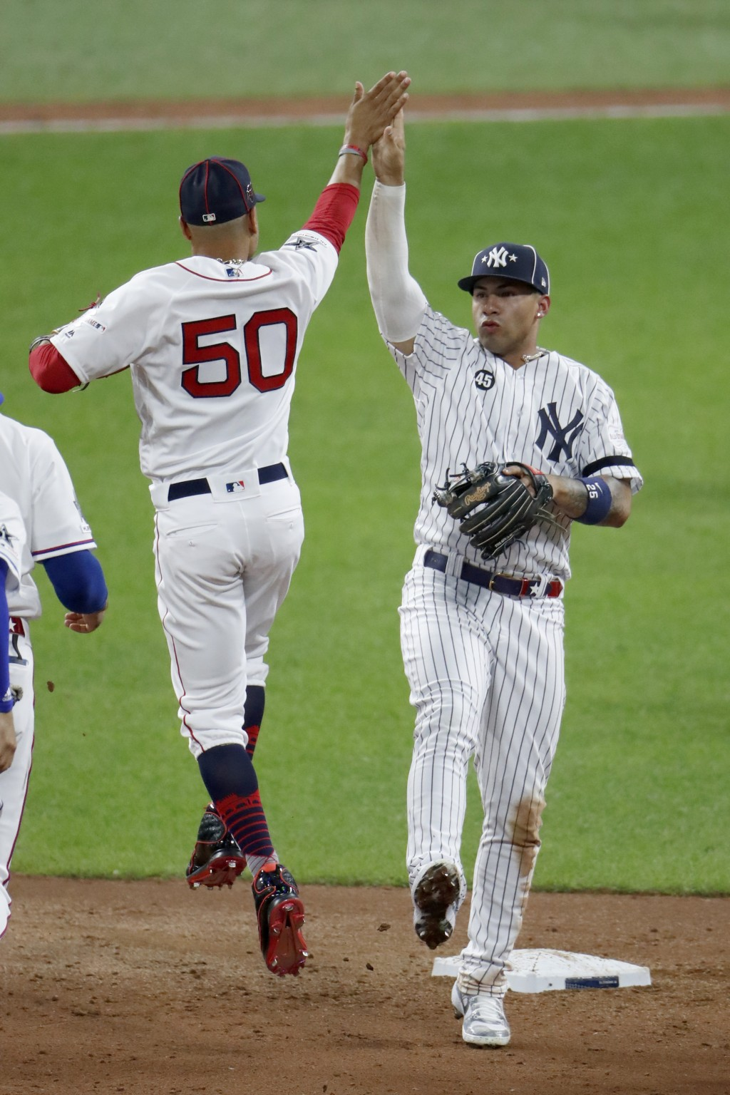 American League's Gleyber Torres, of the New York Yankees, and Mookie Betts (50), of the Boston Red Sox, celebrate the American League's 4-3 victory o...