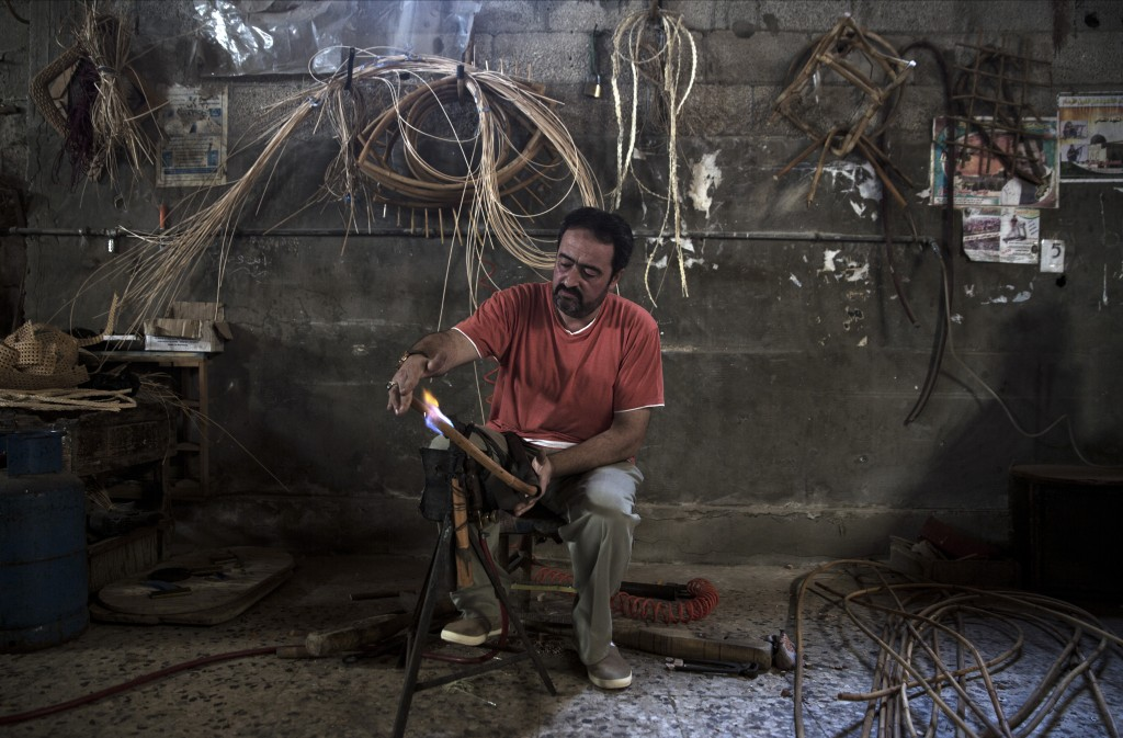 In this Saturday, July 6, 2019 photo, Palestinian Tarek Khalaf uses a flame to form bamboo at his family's workshop in Gaza City. Talk about old Gaza,...