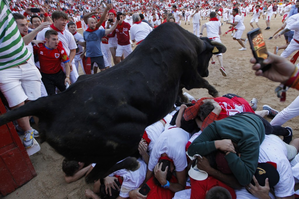 A cow jumps over revellers following the running of the bulls at the San Fermin Festival, in Pamplona, northern Spain, Wednesday, July 10, 2019. Revel...