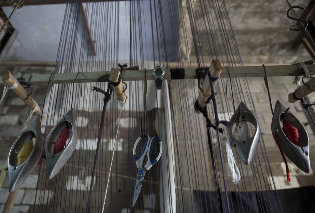 In this Saturday, July 6, 2019 photo, traditional weaving carpets tools hang on a wooden loom at a carpets factory in Gaza City. Talk about old Gaza,
