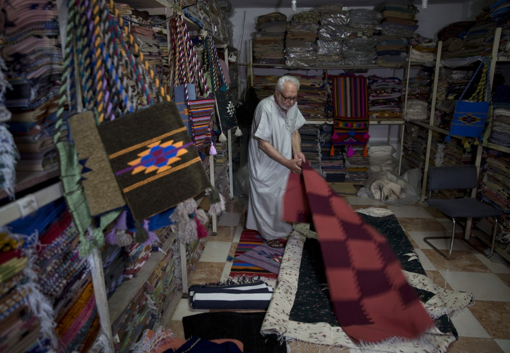 In this Saturday, July 6, 2019 photo, Palestinian Mahmoud al-Sawwaf, the owner of a traditional carpets factory, displays his products in Gaza City.Ta