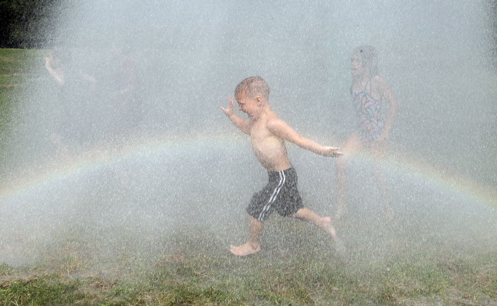 A child rinses himself off after participating in Mud Day at the Nankin Mills Park, Tuesday, July 9, 2019, in Westland, Mich. The annual day is for ki...