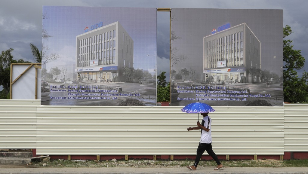 In this Wednesday, April 10, 2019, photo, a man walks past a development site for a Chinese Investment bank in Nuku'alofa, Tonga. China is pouring bil