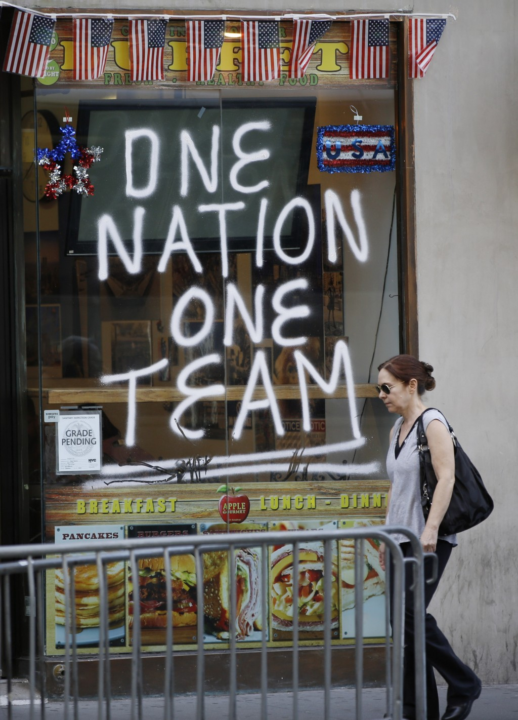 A woman walks past a sign painted on a delicatessen across the street from City Hall one day ahead of a ticker-tape parade for the U.S. Women's soccer
