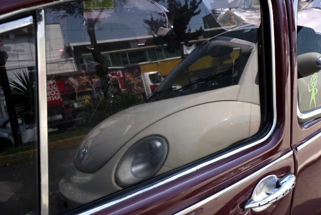 "A newer model of the Volkswagen Beetle is reflected in the window of an older Beetle in a neighborhood of Mexico City known colloquially as ""Vocholand"