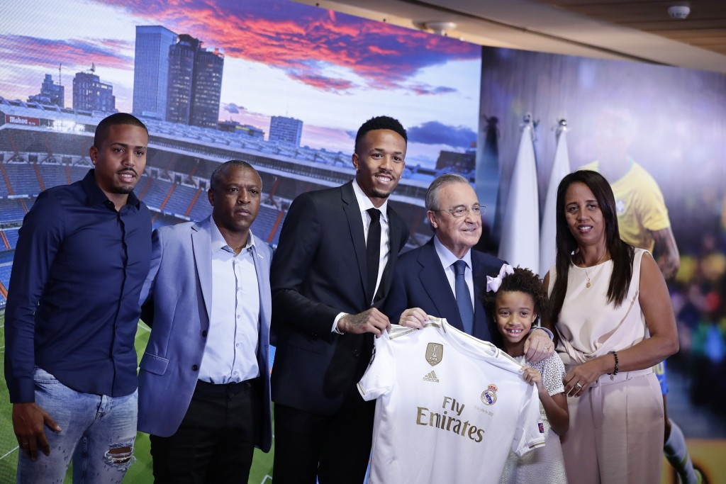 Eder Militao, center left, holds up his new team shirt with Real Madrid's President Florentino Perez and family members of Militao during his official