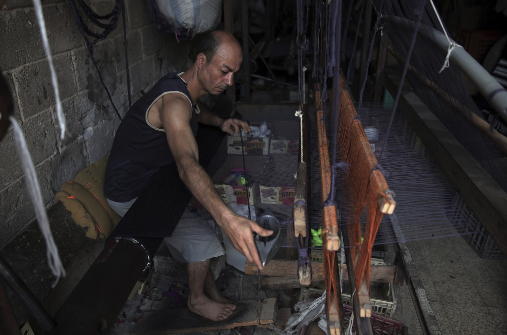 In this Saturday, July 6, 2019 photo, a Palestinian worker weaves carpets on a traditional wooden loom at a carpets factory in Gaza City. Talk about o...