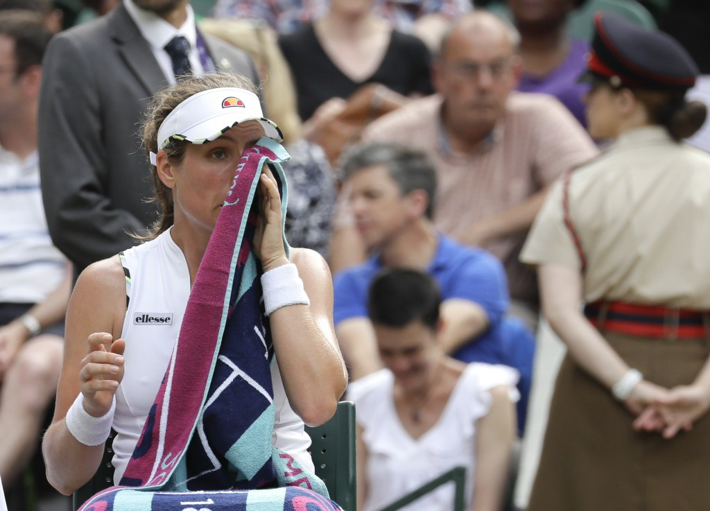 Britain's Johanna Konta wipes her face during a break of a women's quarterfinal match against Czech Republic's Barbora Strycova on day eight of the Wi...