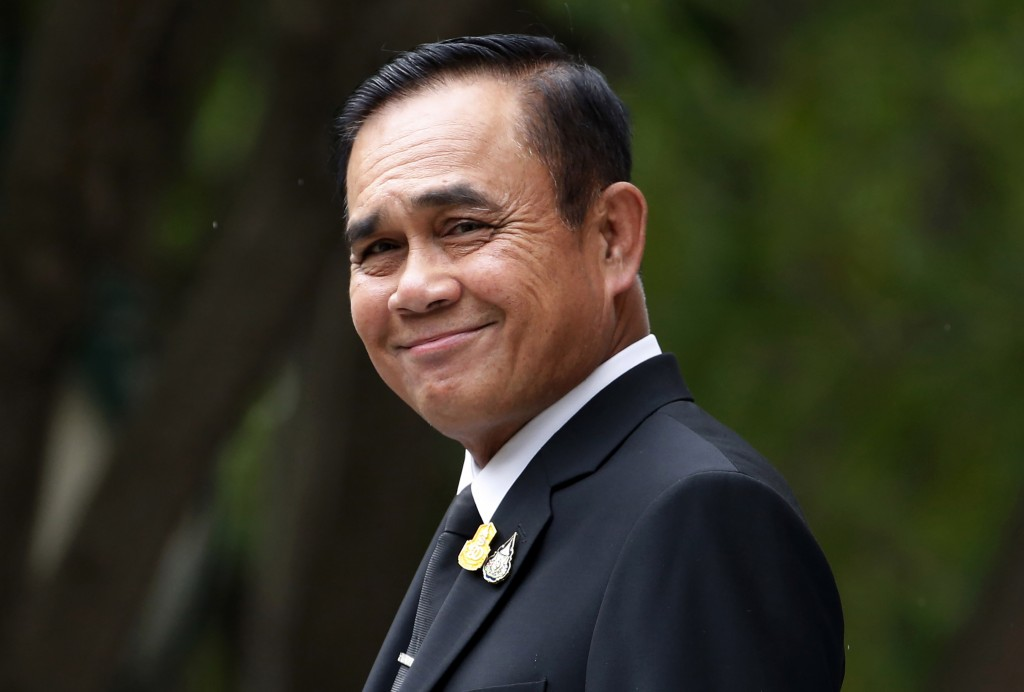 FILE - In this Thursday, June 6, 2019, file photo, Thailand's Prime Minister Prayuth Chan-ocha smiles and talks reporters before a meeting at the gove