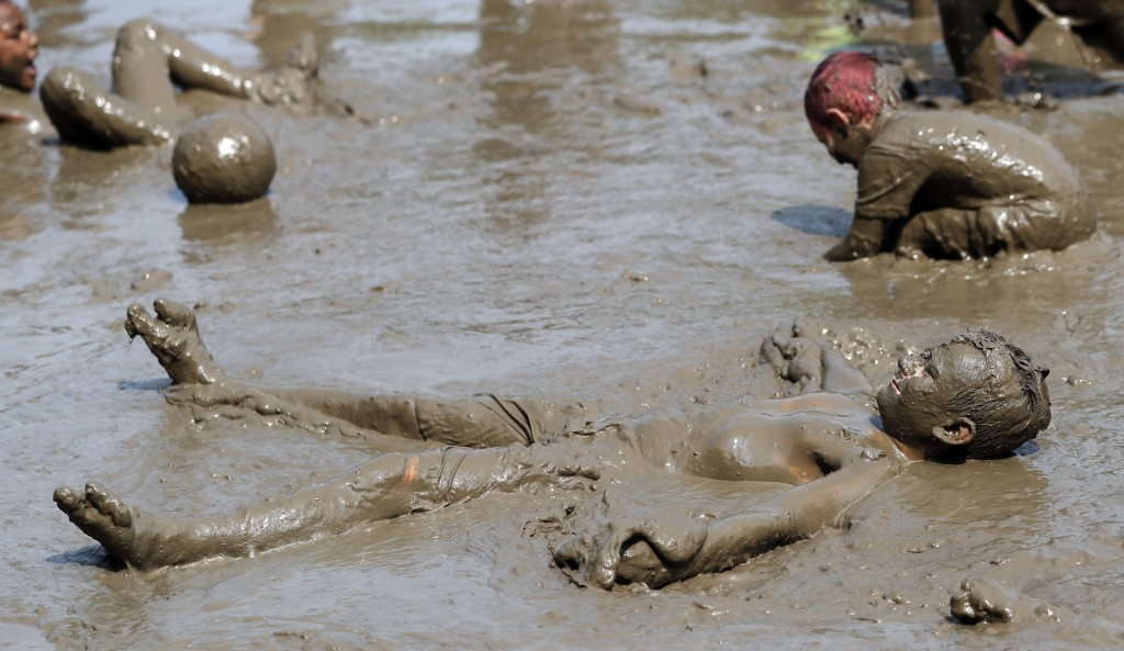 Nathan Jamerson, 10, wallows in the mud during Mud Day at the Nankin Mills Park, Tuesday, July 9, 2019, in Westland, Mich. The annual day is for kids