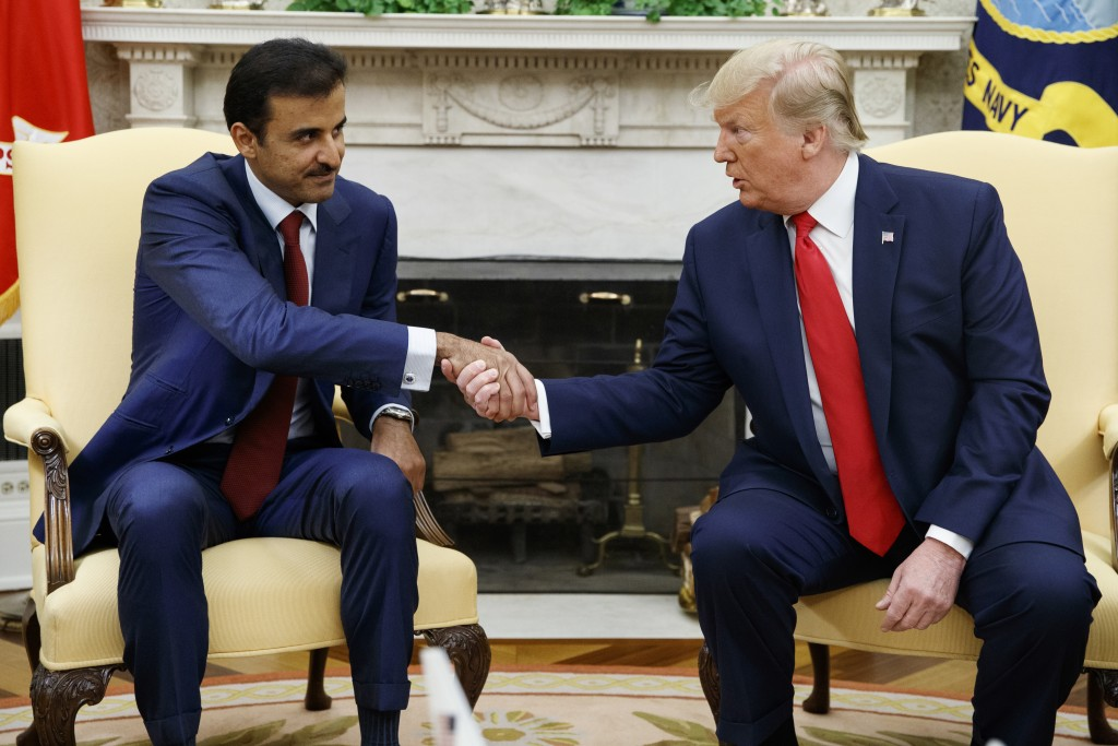 President Donald Trump shakes hands with Qatar's Emir Sheikh Tamim Bin Hamad Al-Thani in the Oval Office of the White House, Tuesday, July 9, 2019, in