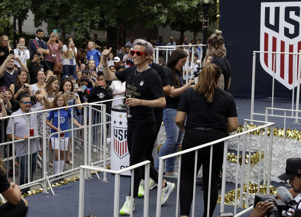 Megan Rapinoe with the U.S. women's soccer team walks onto a float before the start of ticker tape parade along the Canyon of Heroes, Wednesday, July