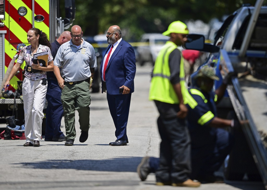 Investigators walk to the crime scene, Tuesday, July 9, 2019, in Cleveland. Police investigating the shooting death of a man in a vacant lot say they ...