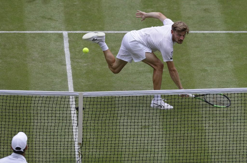 Belgium's David Goffin returns the ball to Serbia's Novak Djokovic, bottom, during a men's quarterfinal match on day nine of the Wimbledon Tennis Cham