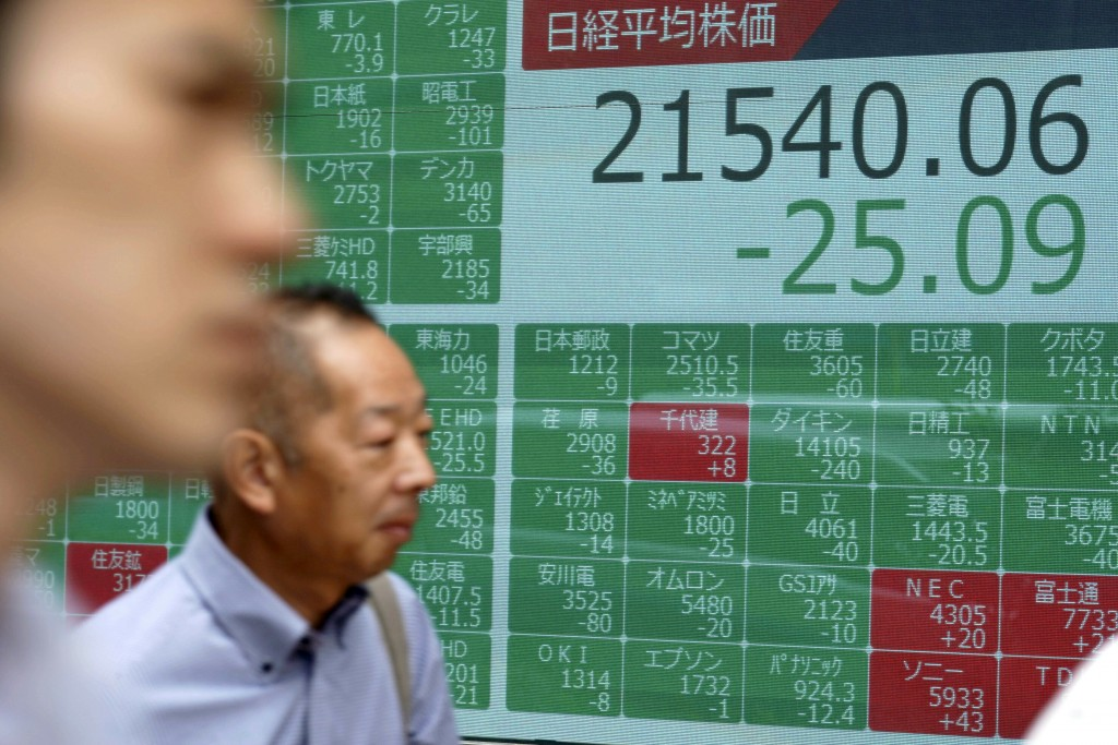 Men walk past an electronic stock board showing Japan's Nikkei 225 index at a securities firm in Tokyo Wednesday, July 10, 2019. Asian shares were mos...
