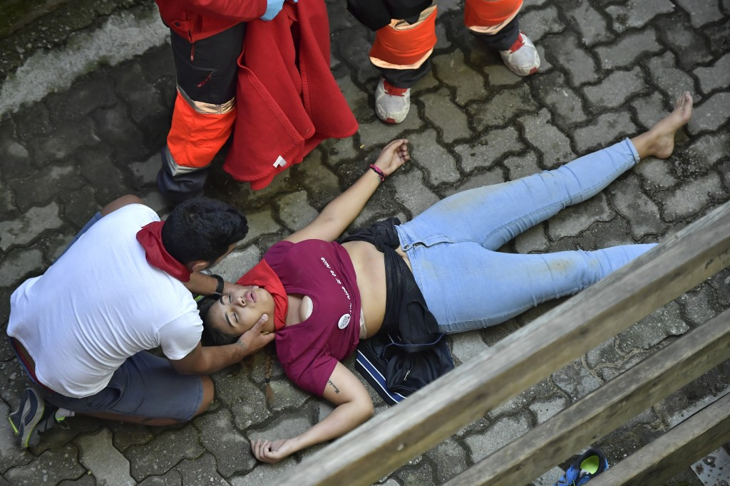 A woman lays on the floor after being injured during the running of the bulls at the San Fermin Festival, in Pamplona, northern Spain, Wednesday, July