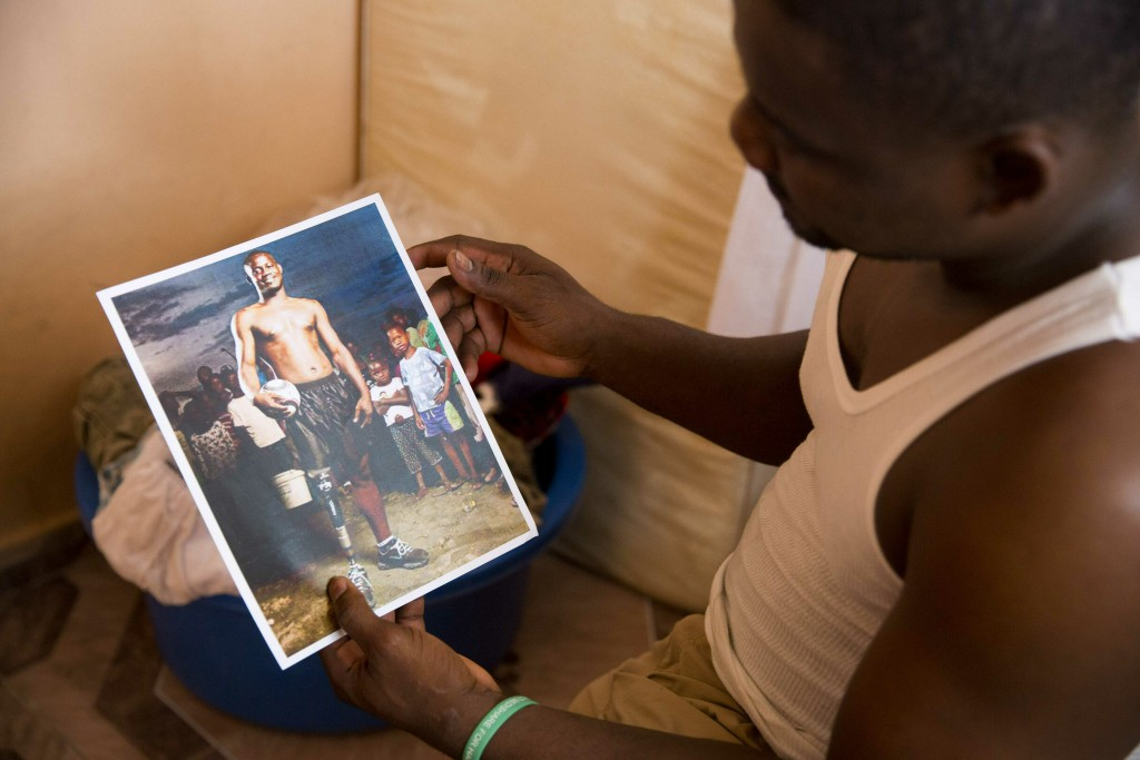 In this June 5, 2019 photo, amputee and prosthetic technician Wilfrid Macena holds a portrait of himself made before the start of a national soccer le...