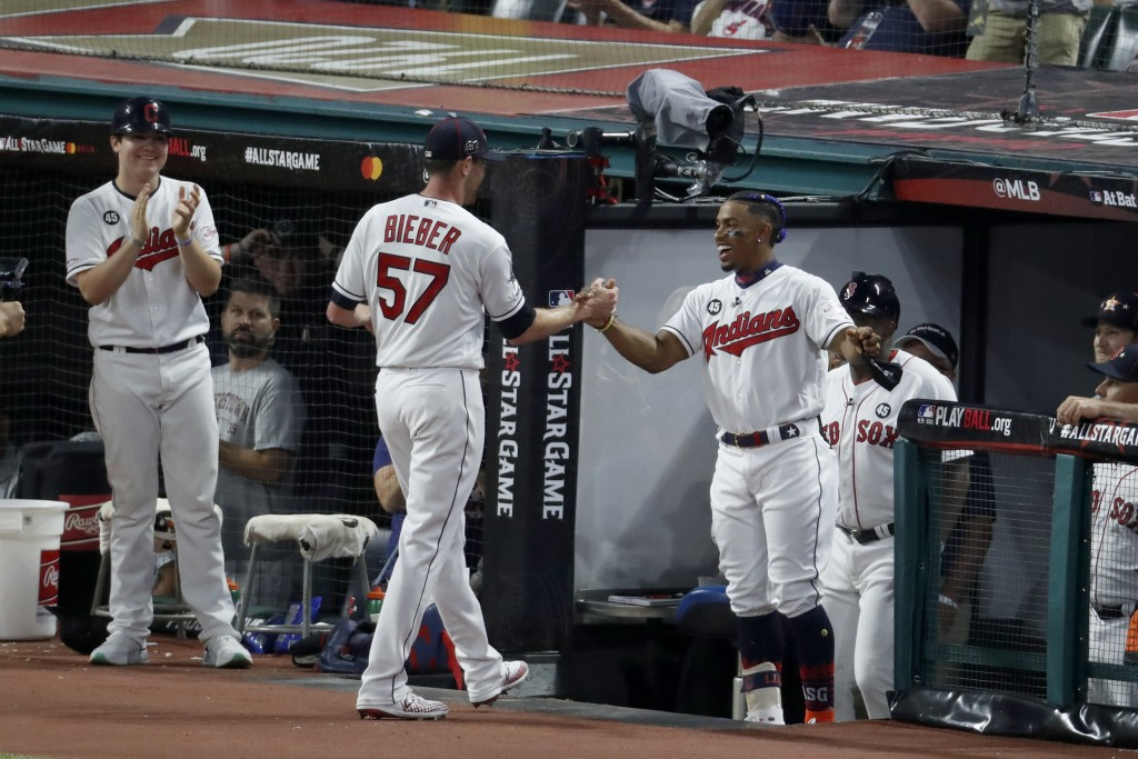 American League pitcher Shane Bieber (57), of the Cleveland Indians, is congratulated by teammate Francisco Lindor, of the Cleveland Indians, after Bi