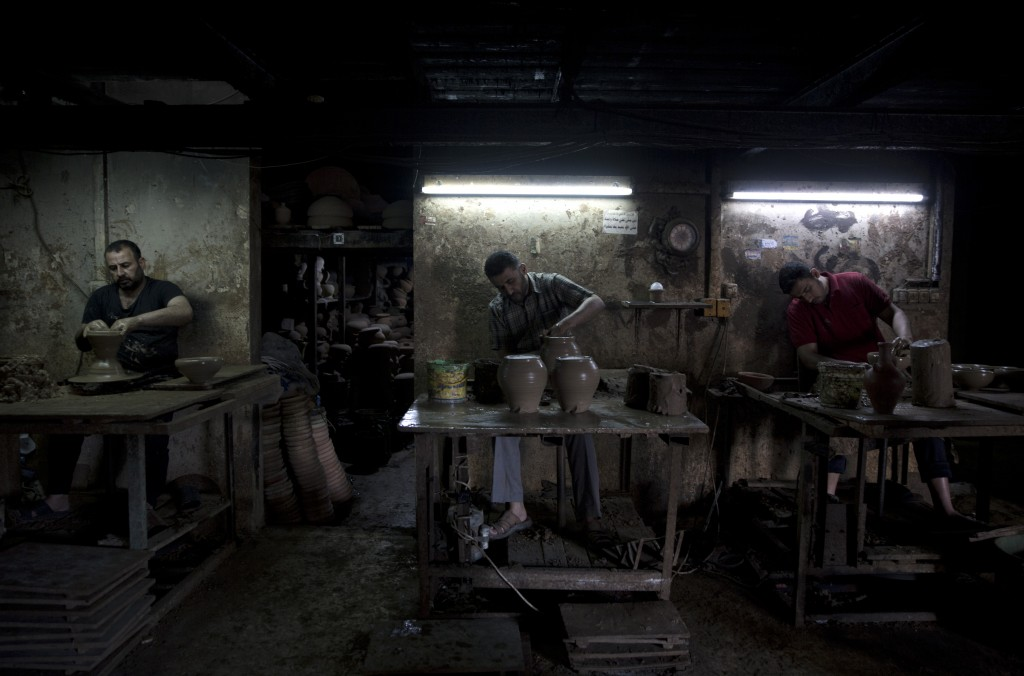 In this Saturday, July 6, 2019 photo, Palestinians, work at a pottery workshop in Gaza City.Talk about old Gaza, and what pops up are images of clay p...