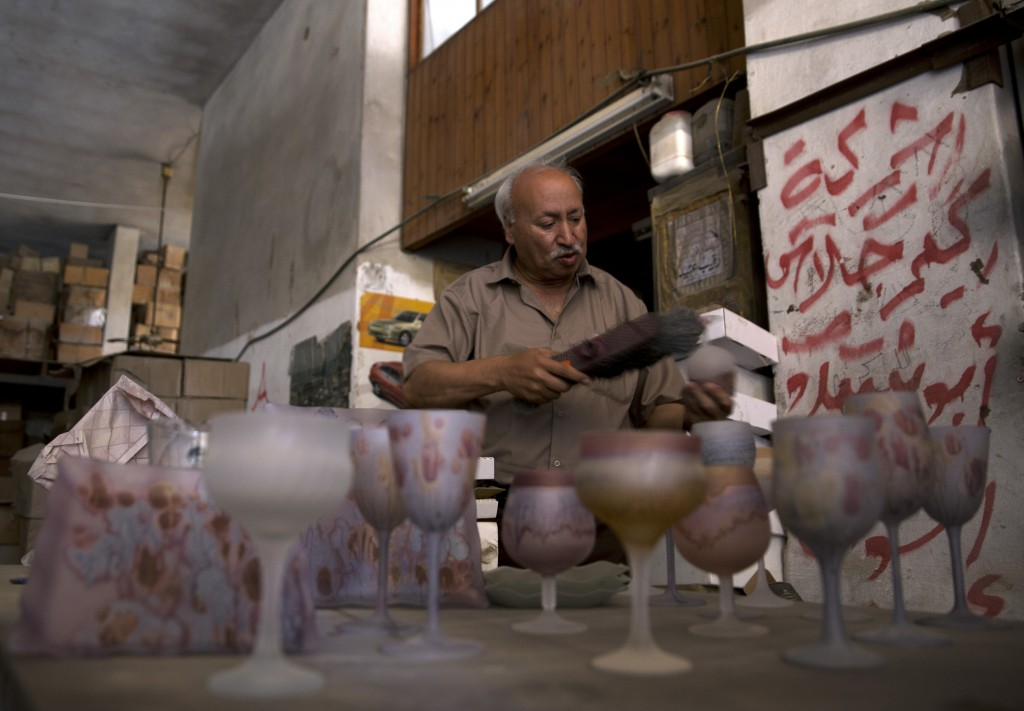 In this Saturday, July 6, 2019 photo, Abed Abu Sedou, removes the dust from samples of hand-painted glasses are displayed on a table in his closed gla...