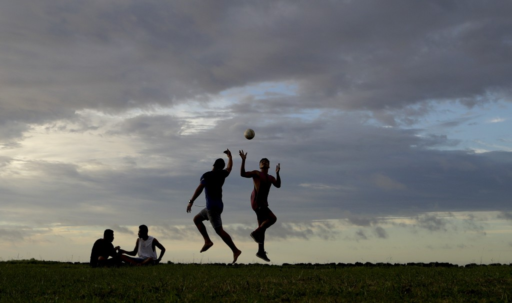 In this Wednesday, April 10, 2019, photo, young men play a game of rugby at sunset in Nuku'alofa, Tonga. China is pouring billions of dollars in aid a