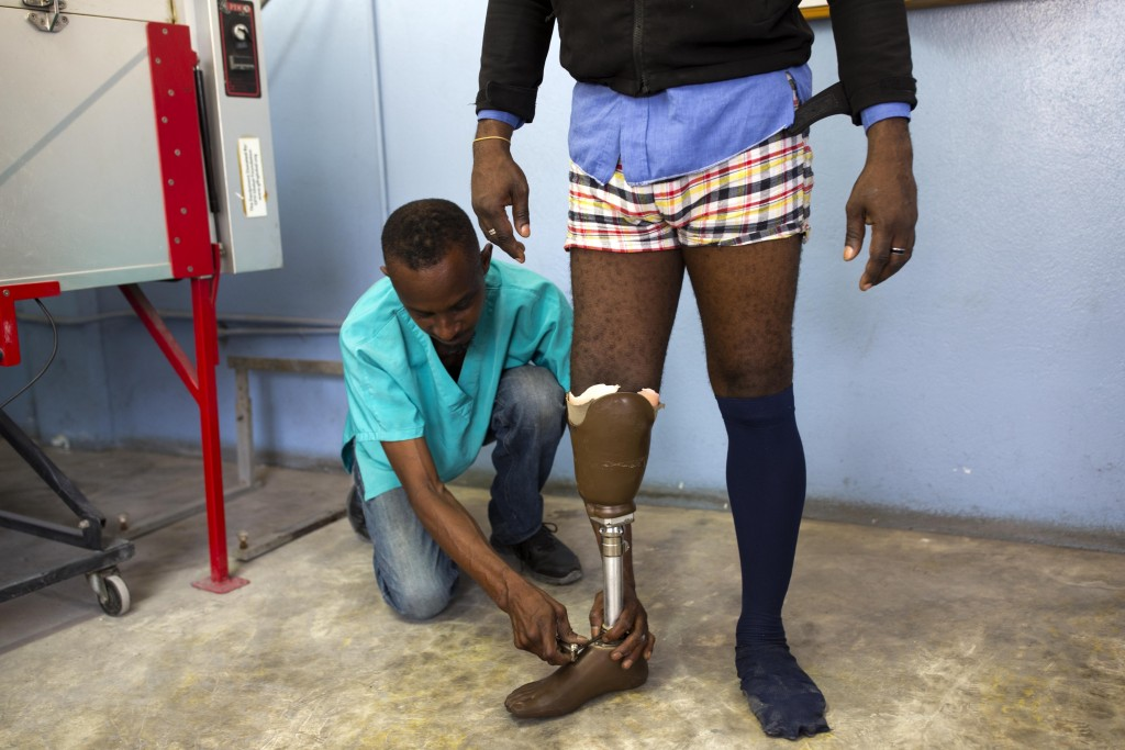 In this June 4, 2019 photo, technician Fritz Lindor fits Fritz Junior Hyppolite with a prosthetic limb at the St. Vincent's Center, in Port-au-Prince,...