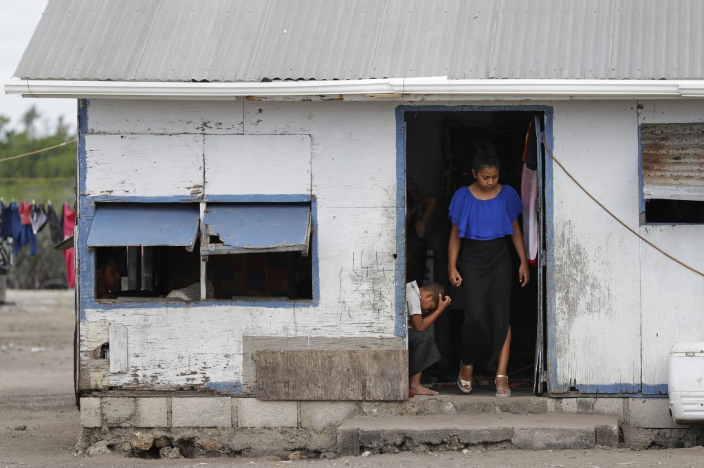 In this Sunday, April 7, 2019, photo, locals prepare to leave their house in Nuku'alofa, Tonga. China is pouring billions of dollars in aid and low-in