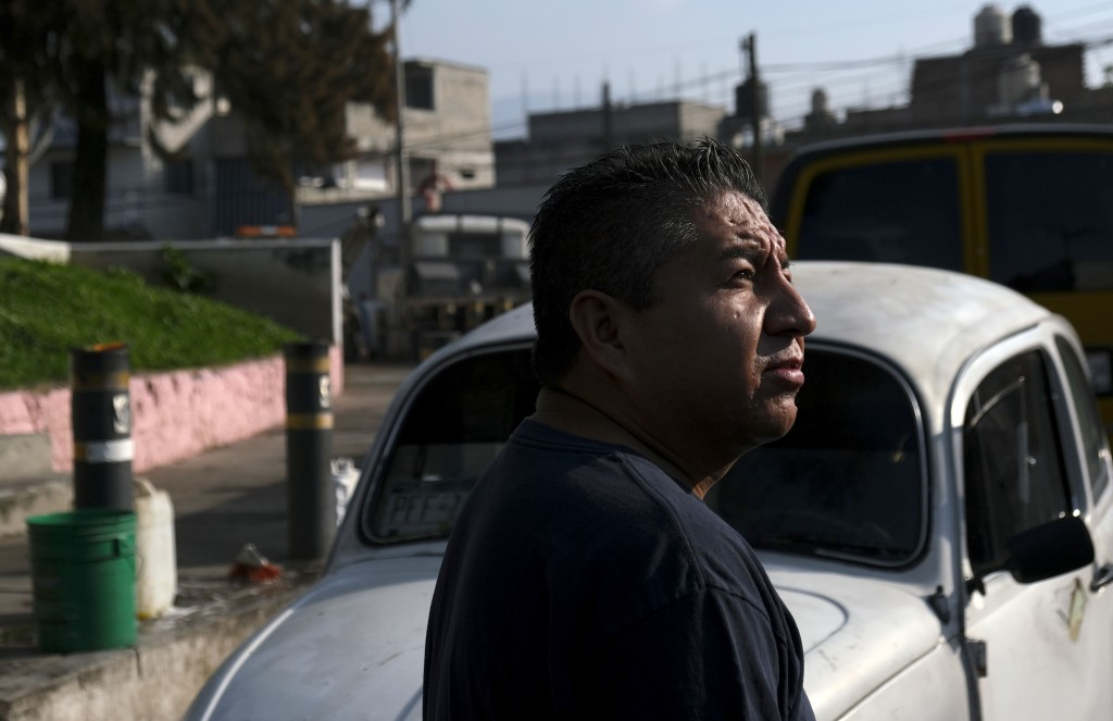 "Mechanic Bernardo Garcia stands in front of his Volkswagen Beetle in a neighborhood of Mexico City known colloquially as ""Vocholandia,"" for its love o"