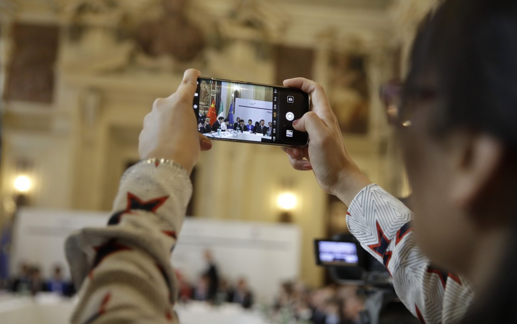 A Chinese journalist takes pictures on the occasion of the Italy-China Financial forum, at Palazzo Marino town hall, in Milan, Italy, Wednesday, July