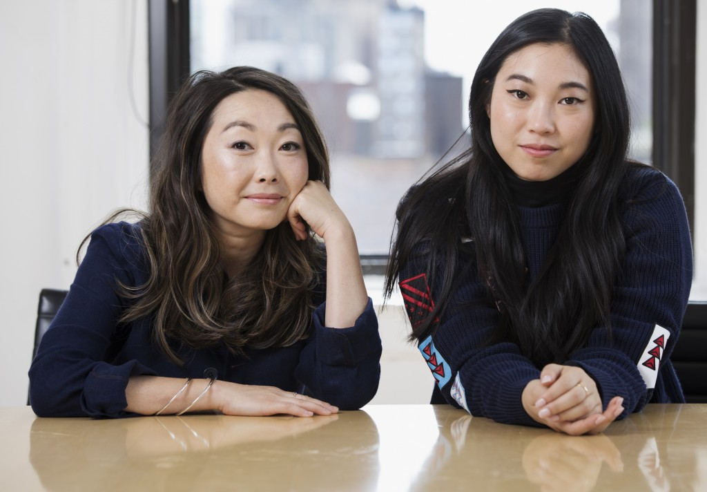 """This June 12, 2019 photo shows filmmaker Lulu Wang, left, and actress Awkwafina posing in New York to promote their film, """"The Farewell."""" (Photo by Br"""