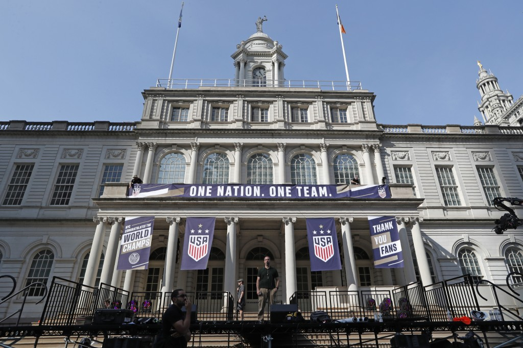 A man tests the microphone on a stage in front of New York's City Hall, decorated with banners in preparation for a ceremony with the Mayor Bill de Bl