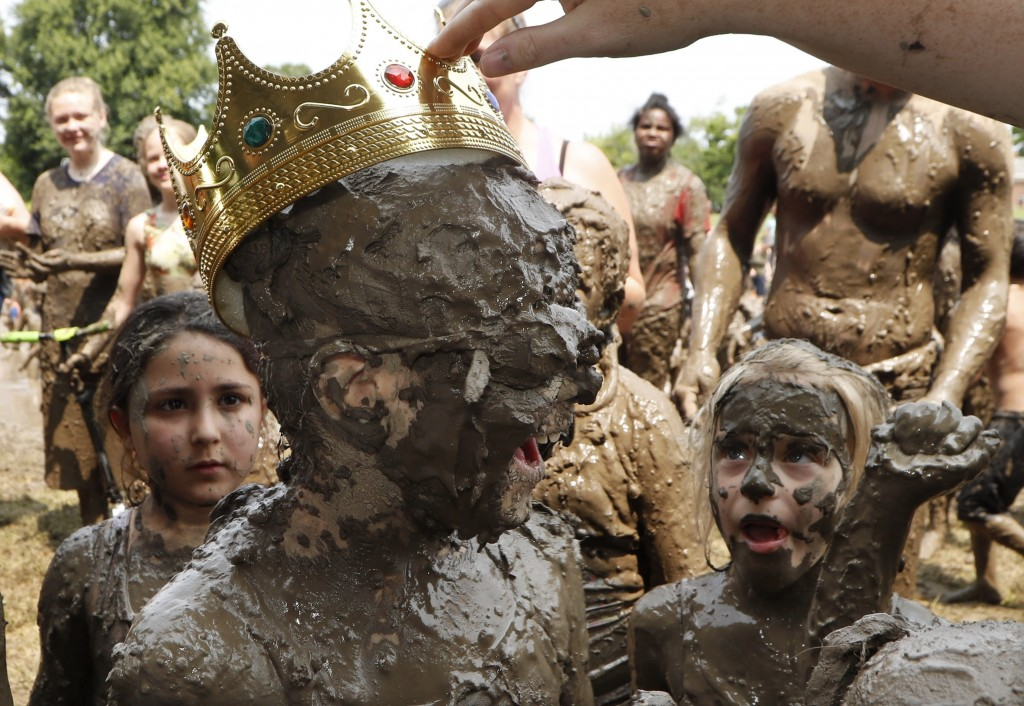 Kids watch as Riley Tulgetske is crowned Mud Day Queen during Mud Day at the Nankin Mills Park, Tuesday, July 9, 2019, in Westland, Mich. The annual d