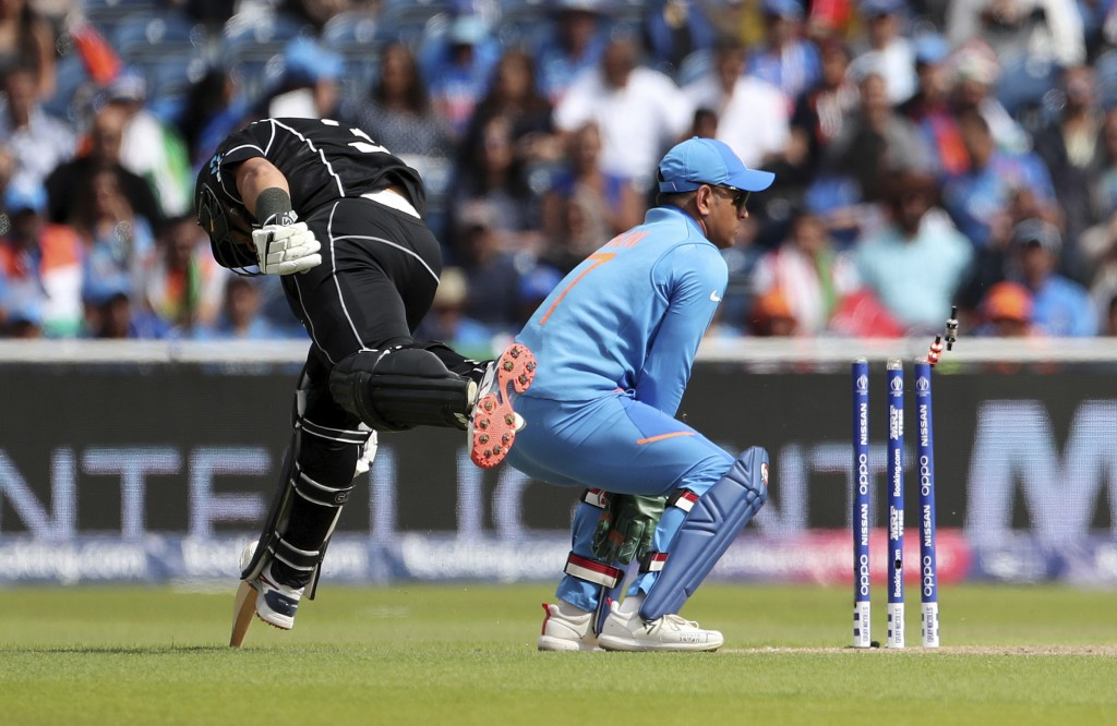 India's MS Dhoni, right, breaks the stumps to run-out New Zealand's Ross Taylor, left, during the Cricket World Cup semi-final match between India and