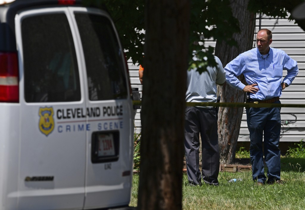 Police officers work at the scene where several bodies were found, Tuesday, July 9, 2019, in Cleveland. Police investigating the shooting death of a m