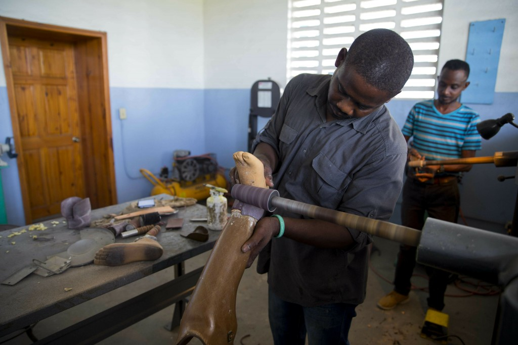 In this May 8, 2019 photo, former welder Wilfrid Macena uses a grinding machine to repair a prosthetic limb at a workshop in the St. Vincent's Center,